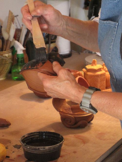 Photo of my mother at work glazing a squirrel pot