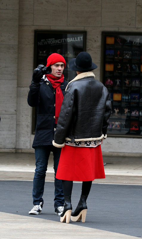 Photo of photographer in red hat talking with model in red skirt - taken by Joana Miranda