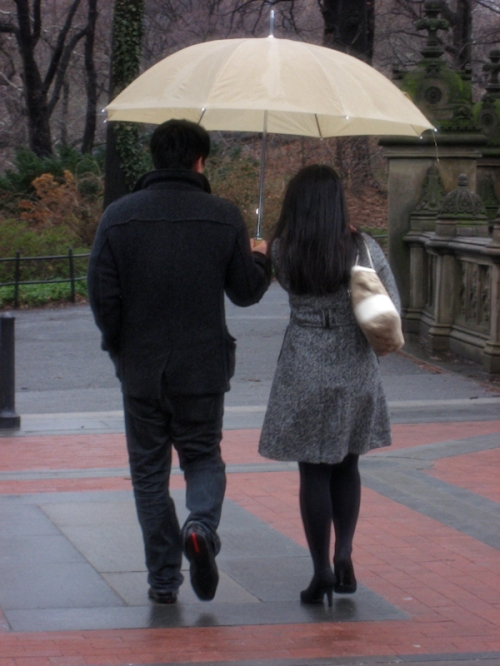 Photo of Asian couple walking in the rain, taken by Joana Miranda