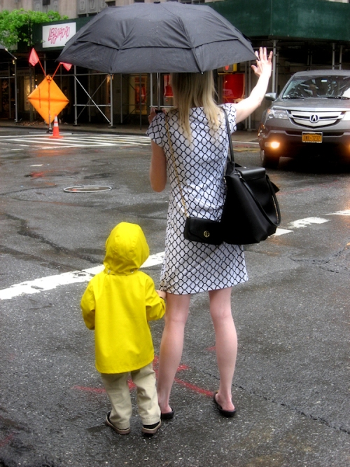 Photo of child in yellow slicker holding on to his mom's dress as she hails a taxi in NYC, taken by Joana Miranda