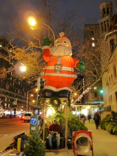 Photo of blow-up Santa doll at tree stand in Manhattan, taken by Joana Miranda