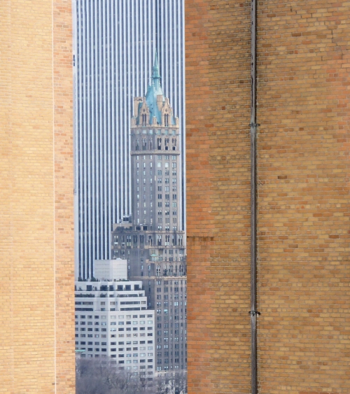 Photo of NYC building seen between two other brick buildings, taken by Joana Miranda