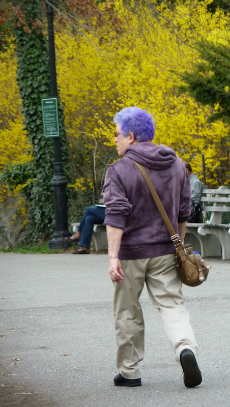 Photo of woman with lavender hair walking against yellow forsythia bushes, taken by Joana Miranda