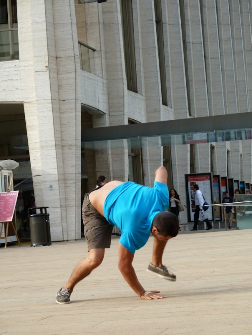 Photo of man in blue shirt and shorts doing a one-handed acrobatic stunt, taken by Joana Miranda