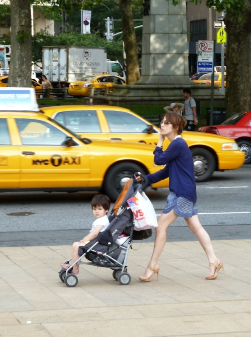 Photo of woman in high heeled sandals and mini skirt pushing baby carriage, taken by Joana Miranda