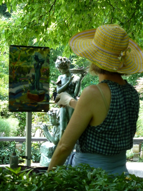Photo of woman painting at the Conservatory Garden in Central Park, photo taken by Joana MIranda