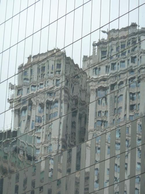 Reflection of stone Art Deco building in sky scraper, taken by Joana Miranda
