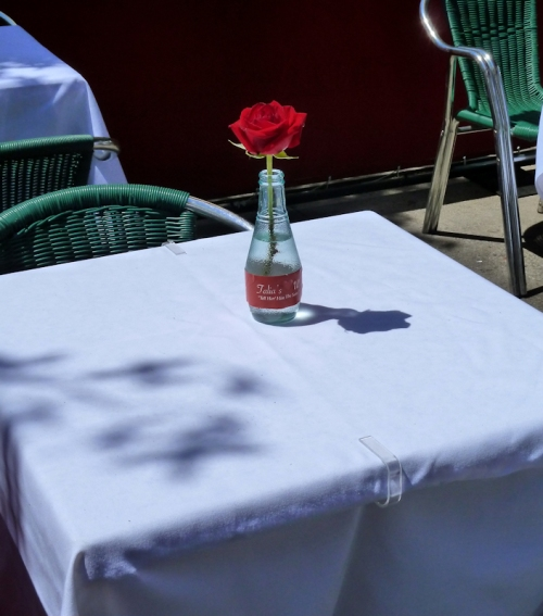 Photo of white table cloth and single rose in Upper West Side cafe, taken by Joana Miranda