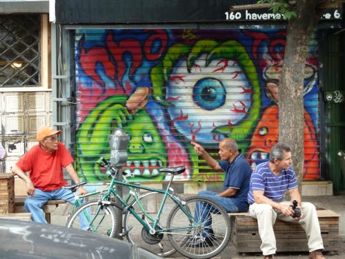 Photo of 3 men sitting in front of wall of graffiti in Williamsburg, NY