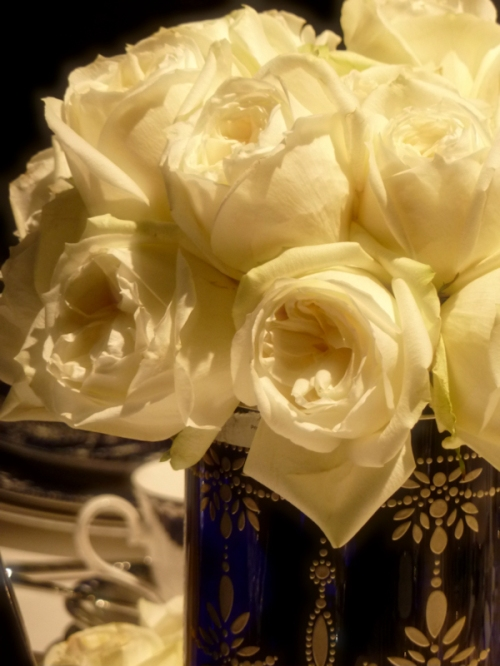 Photo of white roses in blue and gold glass vase, taken by Joana Miranda
