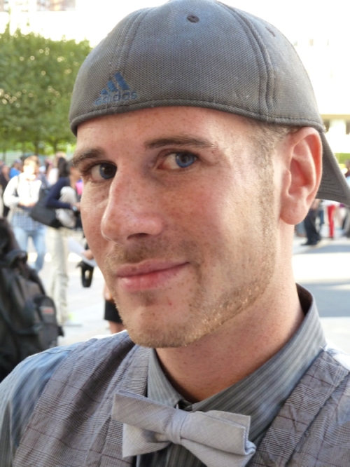 Photo of young man with very blue eyes, bow tie and backwards baseball cap, taken by Joana Miranda at 2012 Mercedes Benz Fashion Week
