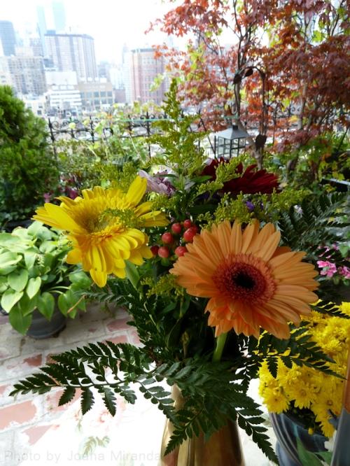 Bouquets of flowers atop table on rooftop terrace, taken by Joana Miranda