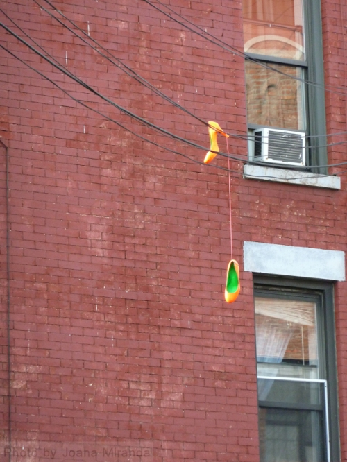 Photo of orange and green heels strung on a telephone wire in Brooklyn, taken by Joana Miranda