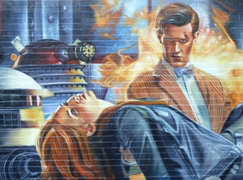 Photo of graffiti wall painting showing man in a suit carrying lifeless body of a woman, taken by Joana Miranda