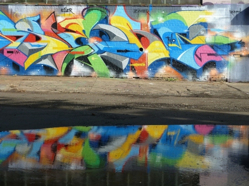 Photo of colorful graffiti and its reflection in a puddle