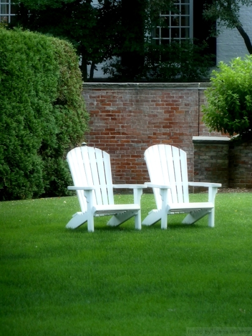 two white adirondack chairs on green lawn