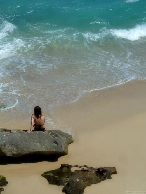 woman sitting on a rock near the ocean