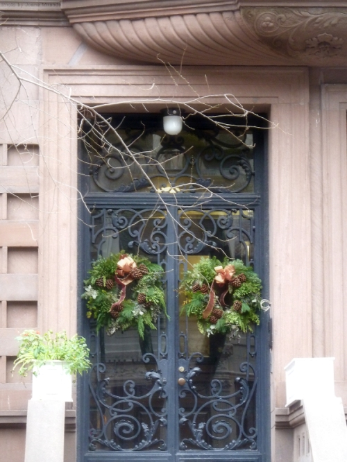 Doorway in NYC with iron grill work and holiday wreaths