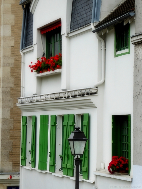 Green shutter and red geraniums in Montmartre